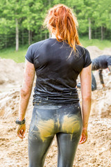 Back of a redhead young woman with messy dirty and muddy sports clothing outdoors.