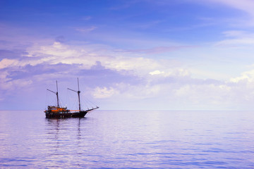 Wooden sailboat, or pinici, in vast Indian ocean under cloudy sky on sunrise, Indonesia. Seascape for wallpaper or background.