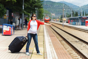 young european pregnant woman with heavy baggage trying to stop train on railway station for traveling at sunny day