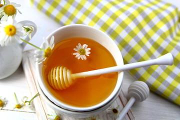 мед в керамической миске с ромашкой.вид сверху