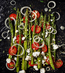 Salad with grilled green asparagus, cherry tomatoes, onion and feta cheese on black background, top view