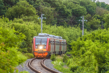 Modern commuter passenger red train is traveling along a single-track railway. Rolling stock with a searchlight on the turn of the railway among green trees.