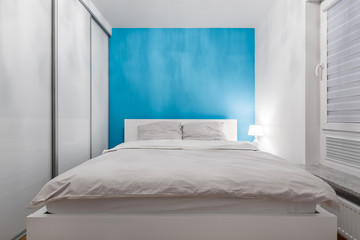 White bedroom with azure wall
