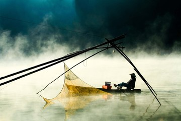Man In Boat On Lake By Fishing Net During Foggy Weather