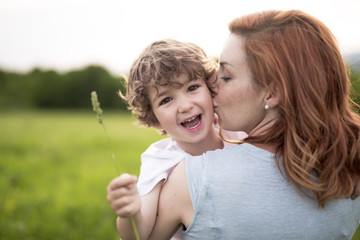 Cute kid boy with his mother on a summer meadow