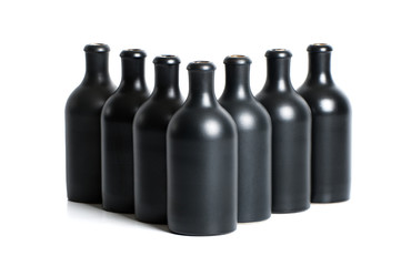 Set of matte black clay bottles on a white background..