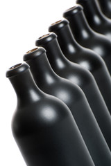 A set of several matte black bottles on a white background close-up..