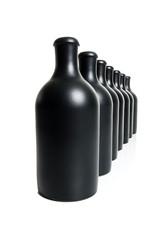 Set of several matte black bottles on a white background..