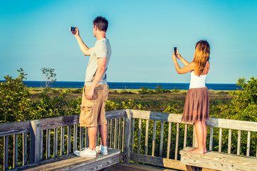 Young Couple traveling, video recording with cell phone.