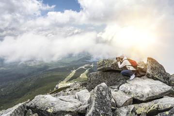 Woman photographer taking photo at mountain peak.
