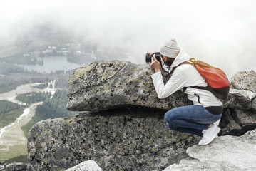 Woman photographer taking photo at mountain peak.
