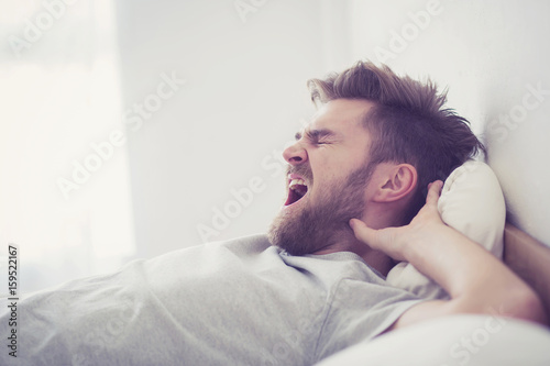 Handsome young american male yawn sleeping in bed at home ...