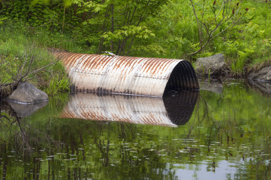 Round metal culvert opening into calm standing water and reflecting on the surface