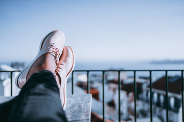 Feet of resting girl with glossy pale pink shoes on the wooden table and touristic resort city with coast and multiple houses in defocused background with copy space for advertising, logo or your text