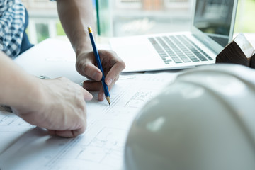 Architect working on real estate project with partner at workplace. Male engineer hand discussing with colleague on living house blueprint at office. Business, people, construction