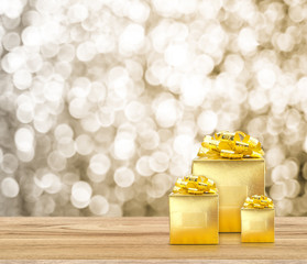 Golden present on wood table top with blur sparkling gold bokeh light background,Gift giving concept,Leave space for adding text for new year or Christmas card