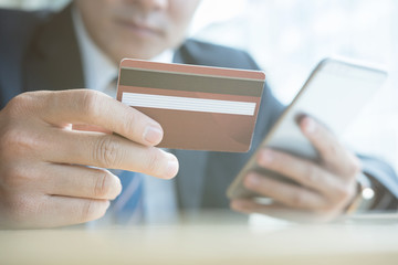 male holding a credit card and using smart mobile phone for online shopping. businessman purchase goods from internet. man make payment on bank website