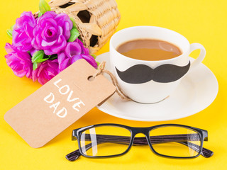 Father's day concept. Happy Father's Day and I LOVE DAD message on note book with pink flower, coffee cup, white gift and black Mustache on yellow background
