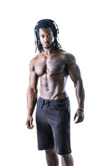 Handsome shirtless muscular black bodybuilder man listening to music with headphones in studio shot isolated on white background