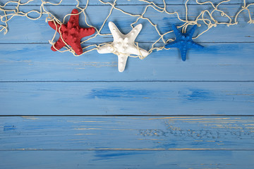 patriotic red white and blue starfish in nautical netting on rustic wood