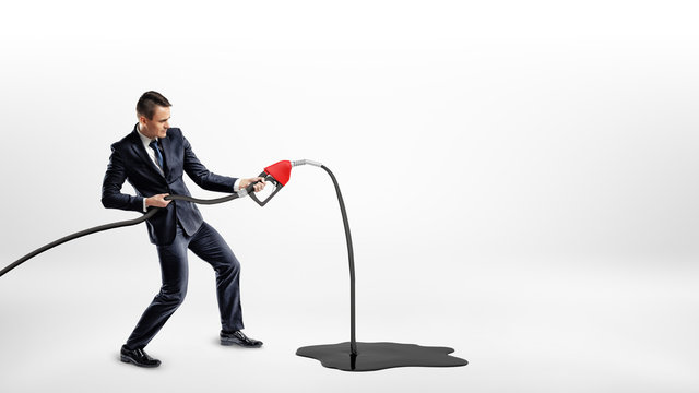 A businessman on white background holding a new red gas nozzle that's leaking oil to a large black puddle.