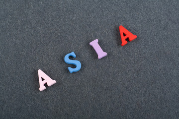 ASIA word on black board background composed from colorful abc alphabet block wooden letters, copy space for ad text. Learning english concept.