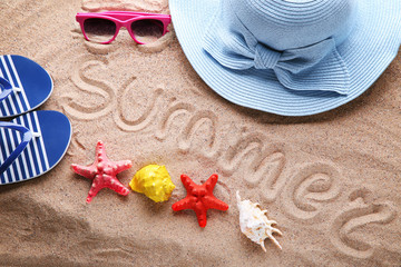 Word Summer written by hand on beach sand with hat, sunglasses and starfish