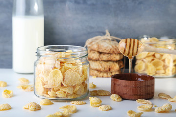 Cornflakes in jar with bowl of honey on wooden table
