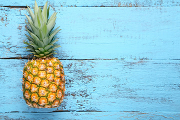Ripe pineapple on blue wooden table