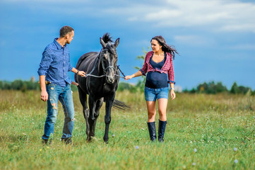 Awaiting the child, walking on the meadow. Young couple - she is a handsome brunette with long hair, pregnant; he is tall and brave, astride a black horse.