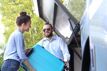 Pasażerka wkłada walizkę do luku bagażowego w autobusie.