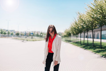 Brunette woman in white jacket stands outside