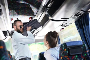 Walizka podręczna. Przystojny mężczyzna pomaga kobiecie włożyć bagaż na półkę w autokarze.