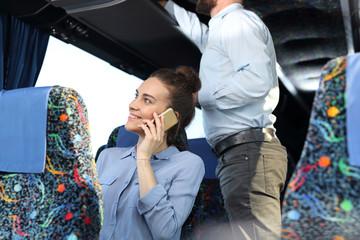 Ludzie w autobusie. Pasażer rozmawia przez telefon w czasie podróży.