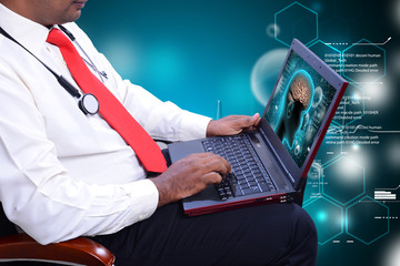 Young doctor looking on laptop