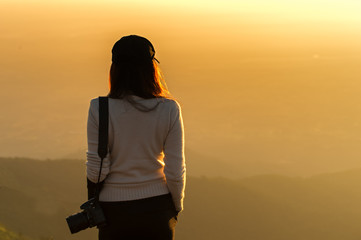 Professional woman photographer see the mountain veiw in the sunrise