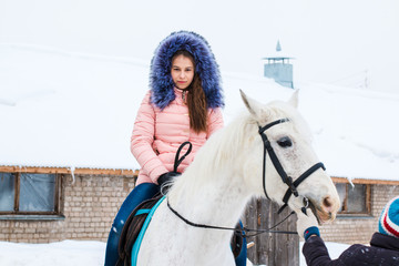 Girl, horse trainer and white horse in a winter