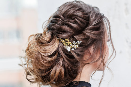 attractive young brunette woman with beautiful hairstyle with hair detail accessory, closeup rear view