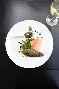 Plate of salmon fillets with fresh herbs, vegetables and balsamic vinegar with a glass of white wine on a black table