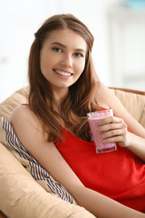 Weight loss concept. Beautiful young woman drinking healthy delicious smoothie at home