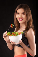 Young athletic woman with a salad