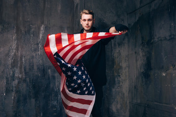 Male USA patriot with flying national flag. Strong man in black cloth on dark studio background. Independence day, confidence, pride, fidelity to the nation, memorial day concept