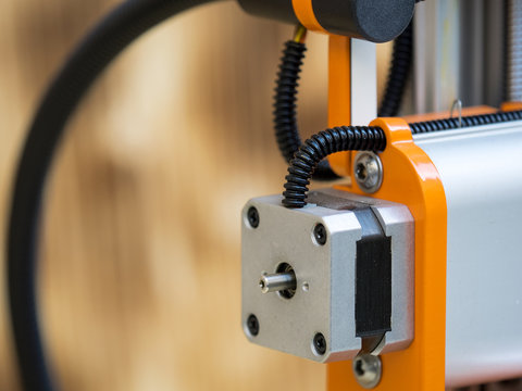 Detail of a stepper motor on a hobby-grade CNC desktop machine, selective focus