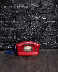 Old, red phone on a black table