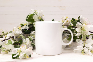 White coffee mug with blossoming apple tree branches.