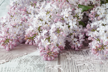 Background with fresh lilac flowers on turquoise painted wooden planks.