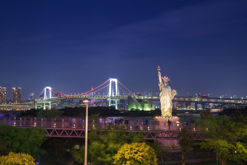 tourists enjoy the view of the Tokyo Bay from Odaiba with the statue of liberty