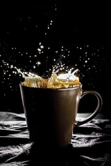 Coffee drop with smoke in the brown glass black background