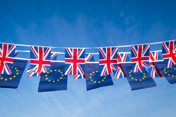 European Union and British Union Jack flag bunting flying in bright blue sky in a statement of the Brexit EU negotiations