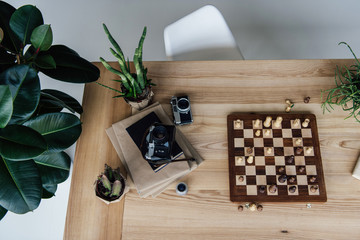 Creative workplace concept with old retro cameras lying on books and chess board during the game